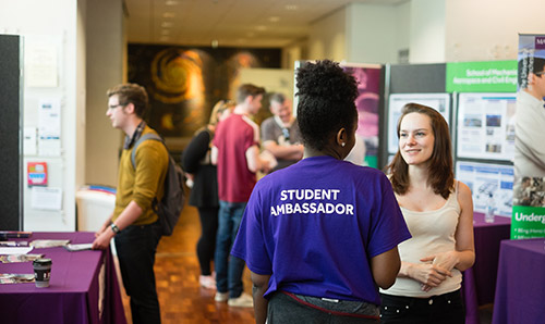 Student ambassador helping out a visitor on an open day