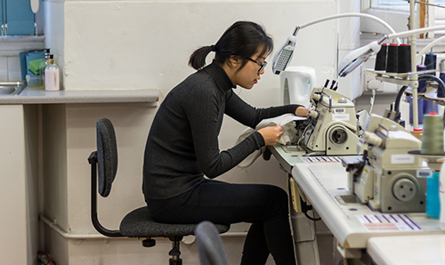 Female student operating a sewing machine