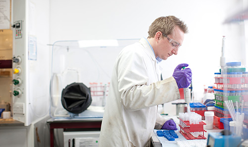 Lab coat-wearing male student squeezing pipette into test tube
