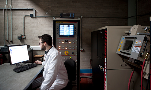 Male researcher working on computer in Dalton Nuclear Institute laboratory