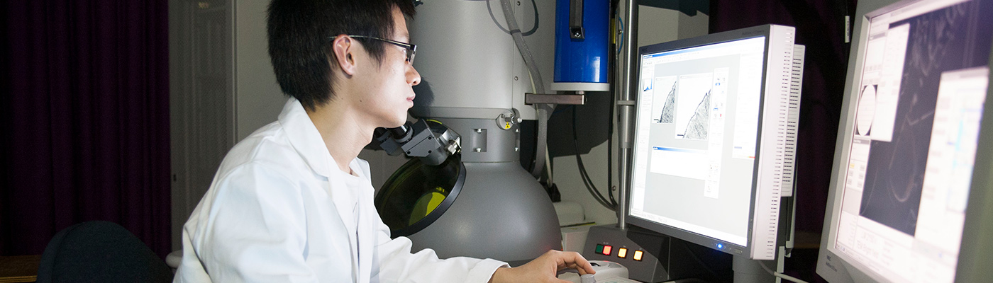 Student assessing microscopy results on computer