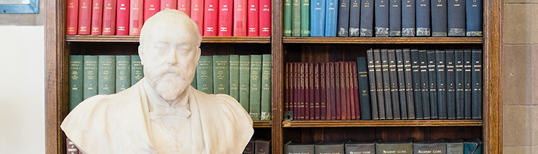 Bust of professor in front of library bookshelf