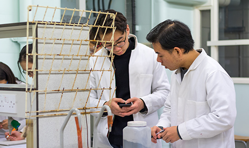 Two male researchers in lab coats looking at information on a mobile phone